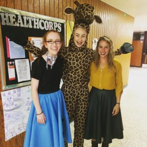 Autumn (far right) celebrates Halloween at Ada High School with two HealthCorps champions who are involved in all of her clubs