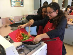Living Labs Students using stove top, putting cut vegetables onto a pan for HealthCorps cooking club